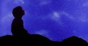AJ0GTE Square image of a small child in profile looking up at a star filled night sky.